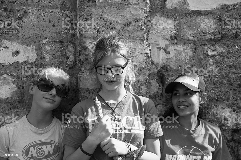 three teenage girls standing against wall stock photo