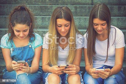 istock Three Teenage Girls Using Their Smartphones 981871638