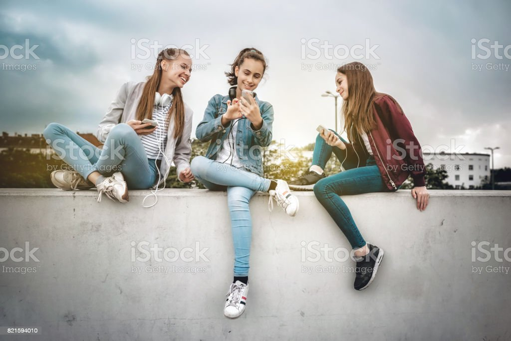 three teenage girls with smartphones on concrete wall stock photo
