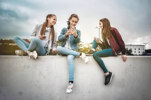 three teenage girls with smartphones on concrete wall three happy teenage girls sitting outdoors on concrete wall and looking at smartphone leisure equipment stock pictures, royalty-free photos & images