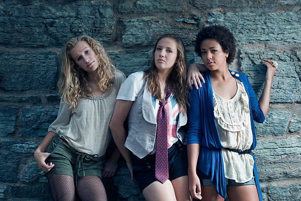 Three Teenage Girls, Young Women Looking Cool by Stone Wall stock photo