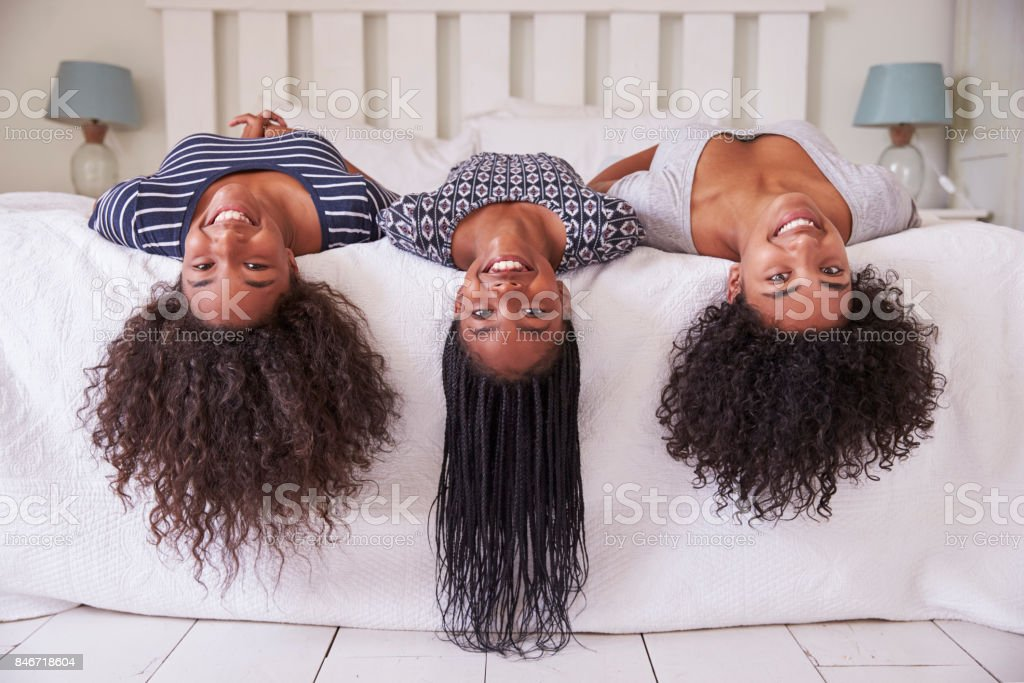 Three Teenage Sisters With Long Hair Lying On Bed At Home stock photo