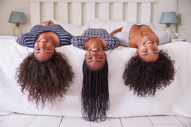 three teenage sisters with long hair lying on bed at home - day in the life series stock pictures, royalty-free photos & images