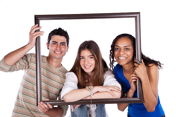 Three teenaged friends posing in a picture frame stock photo