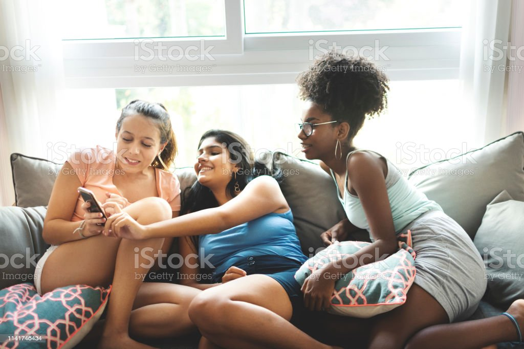 Três meninas do adolescente, no sofá, olhando o telemóvel, e se divertindo. - Foto de stock de 16-17 Anos royalty-free