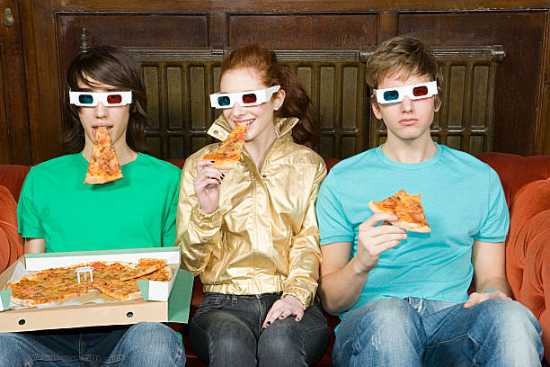 three teenagers eating pizza - nerd boy eating stock photos and pictures