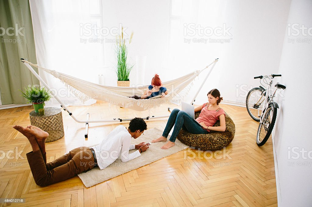three teenagers look down in their digital devices royalty-free stock photo