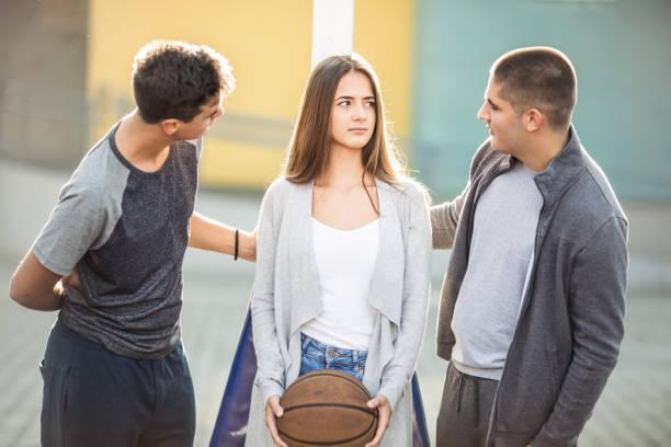 Three teenagers playing basketball stock photo