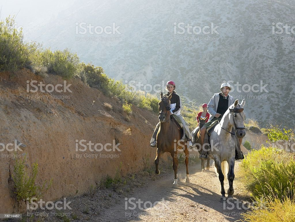 Three teenagers riding horses stock photo