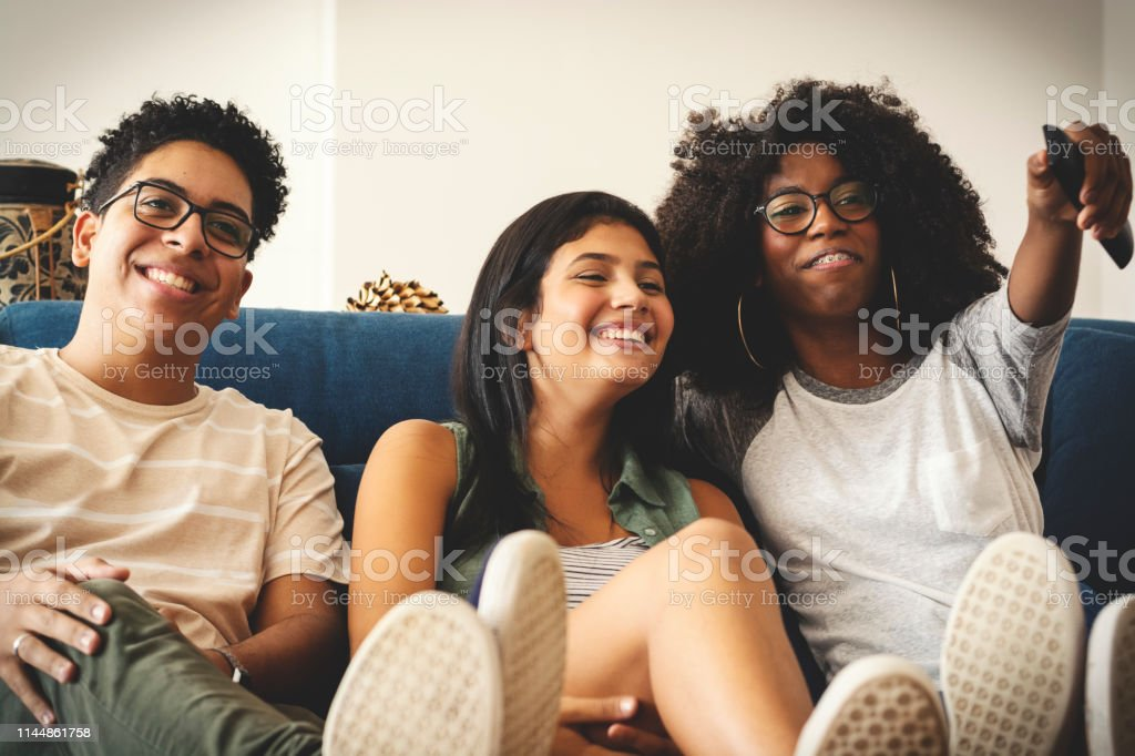 Three teenagers watching tv together and having fun - Royalty-free 16-17 Years Stock Photo