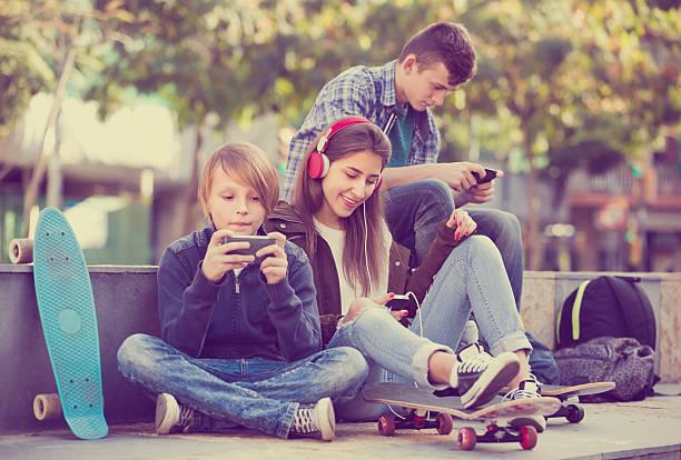 drei teenager mit handy im freien - radio kultur stock-fotos und bilder