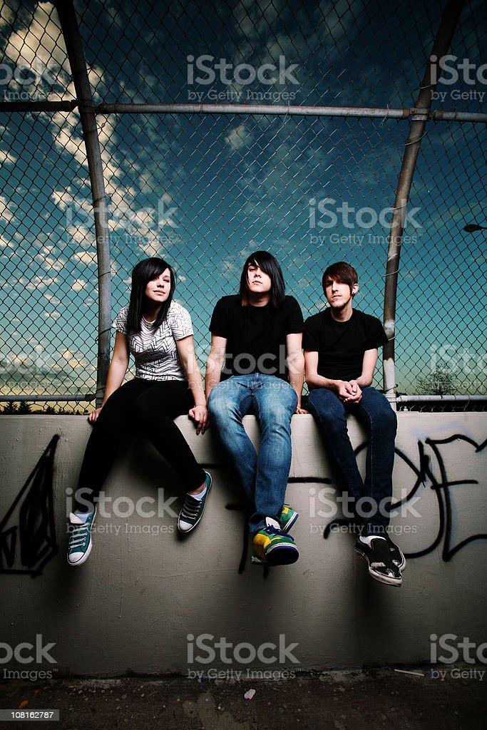Three Teens Sitting on a Wall royalty-free stock photo