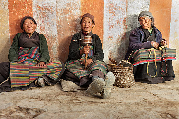 drei tibetischen frauen beten in lo manthang, nepal - nepal tibet stock-fotos und bilder
