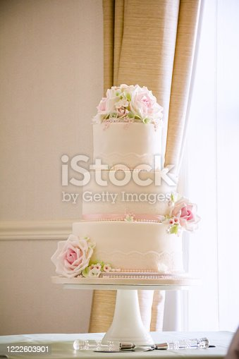 Three tier wedding cake with pale pink sugar roses, set next to a window.