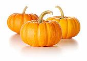 Three tiny orange pumpkins on a white background