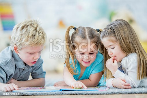 istock Three toddlers reading a book 1064885906