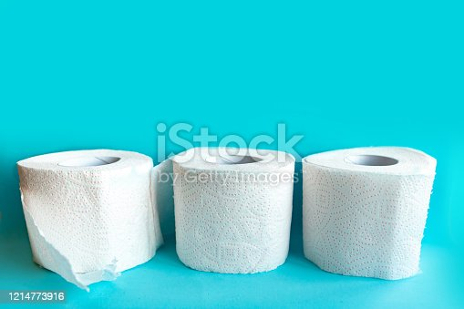 istock Three toilet paper rolls on blue background. Quarantine 2020 concept 1214773916