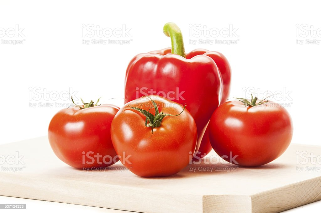 Three tomatoes and a red pepper on a wooden board. stock photo