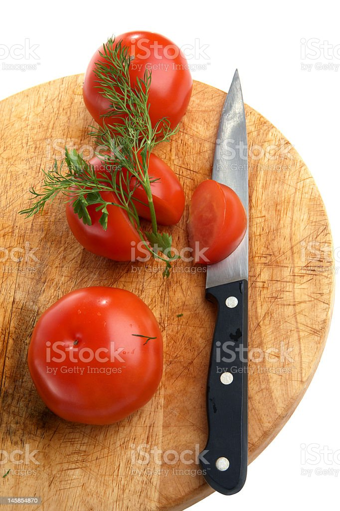 Three tomatoes and knife on a little table royalty-free stock photo
