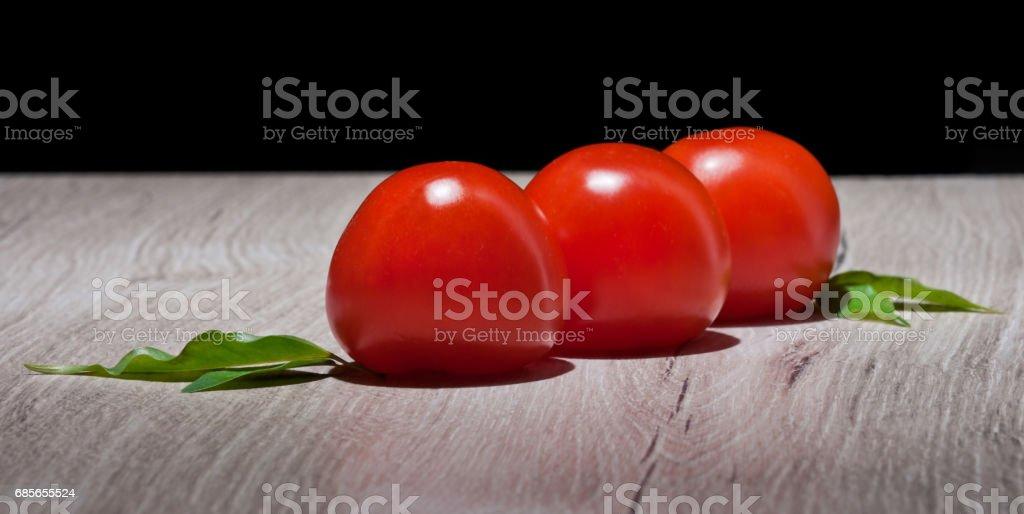 Drei Tomaten auf einem rustikalen Tisch auf einem schwarzen Hintergrund Lizenzfreies stock-foto