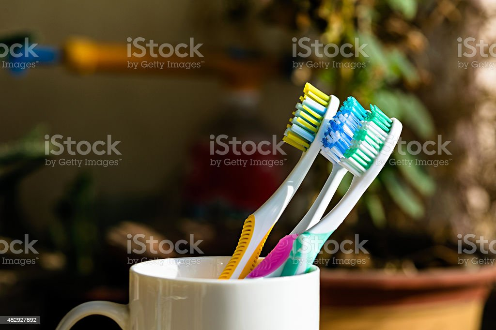 Three Toothbrushes on a cup stock photo