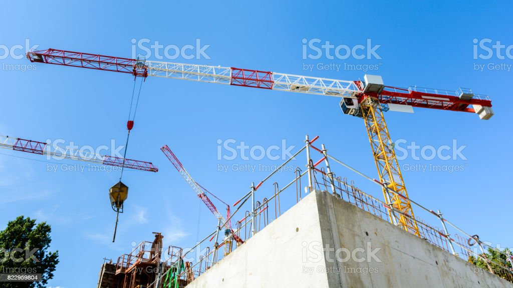 Three tower cranes on a construction site stock photo