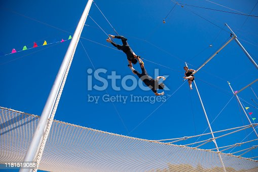 Three trapeze artists playing together in the blue sky