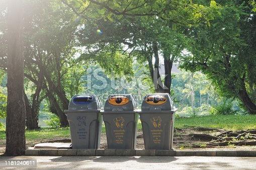 Three trash in the garden. Each bin is separated type of waste. Each trash including icon, Thai and English for specific waste, blue for food, yellow for can plastic bottle paper and bag.