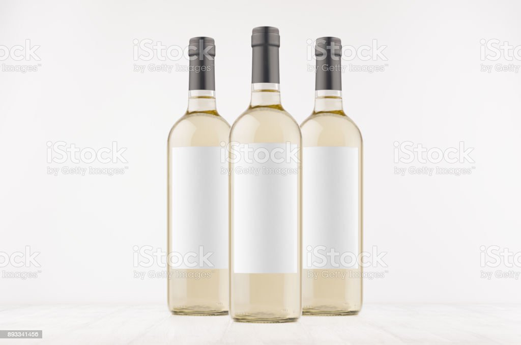 Three trasparent wine bottles with blank white labels on white wooden board, mock up. stock photo
