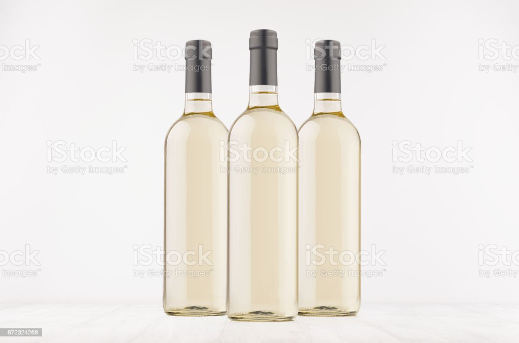 Three trasparent wine bottles with white wine on white wooden board, mock up. stock photo