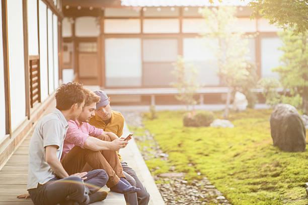 3 つのお客様のために、スマートフォンを見て、日本の寺 ストックフォト
