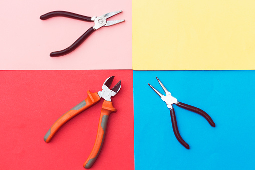 three types of pliers and nail isolated on colorful background