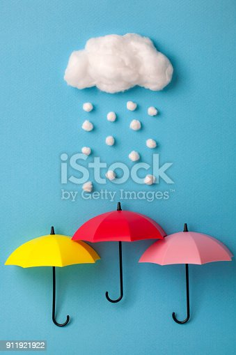 Three umbrellas under the cloud on sky blue background.