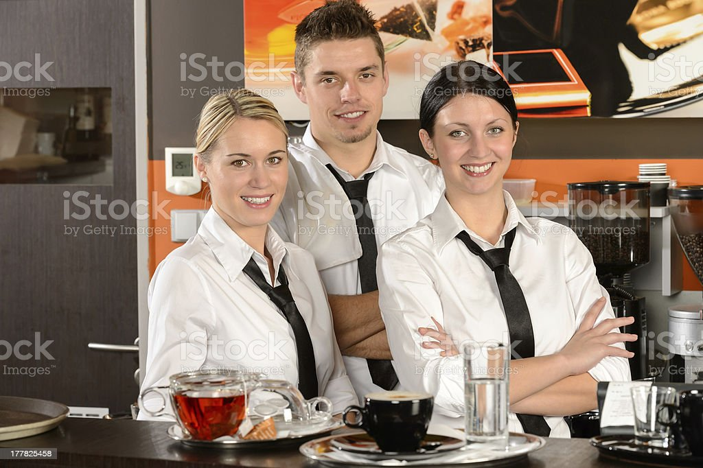 Three uniformed server posing in cafe stock photo