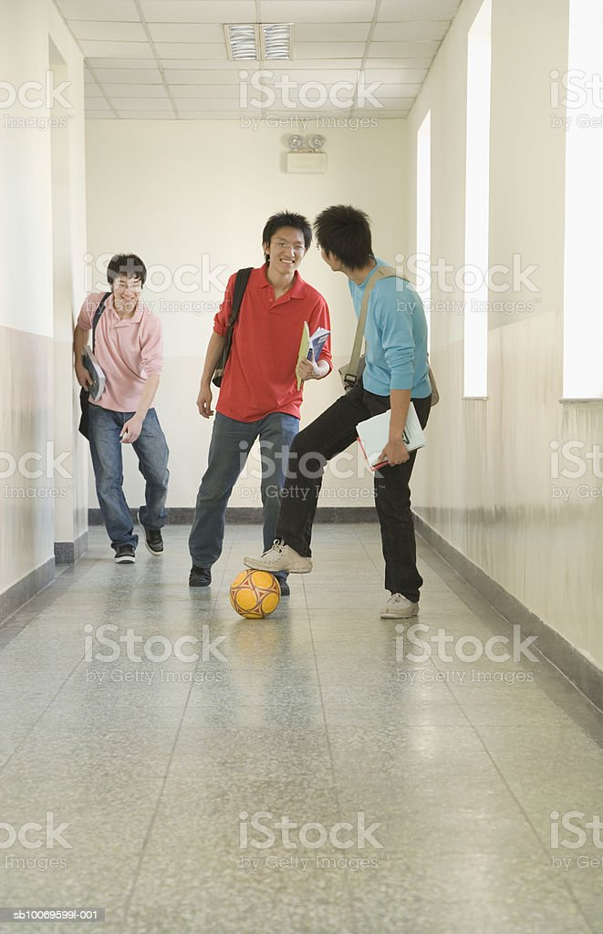 Three university students playing football in hallway foto de stock royalty-free