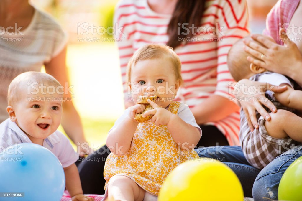 Three unrecognizable mothers outdoors in green nature with their children having picnic. stock photo