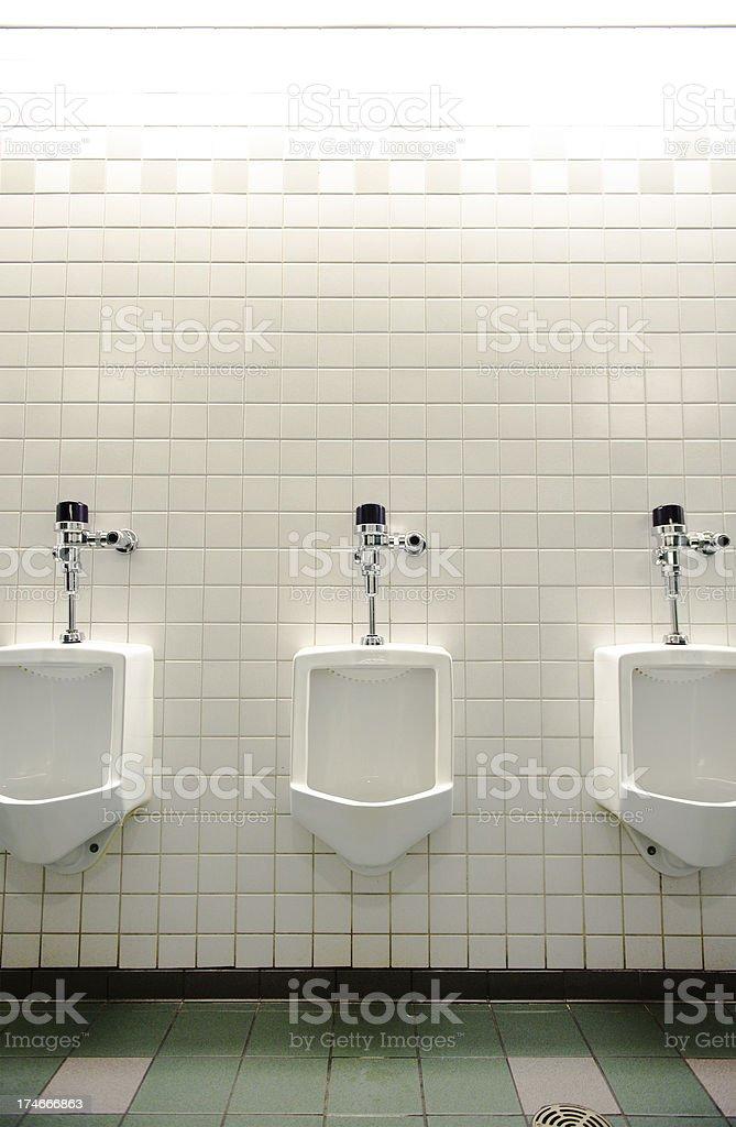 Three urinals in a men's bathroom stock photo