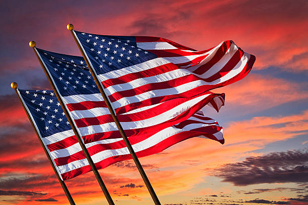 Three US Flags Waving with Red Fire Battle Sky Background stock photo