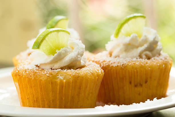 drei vanille cupcakes mit der coconut farbgebung dominieren buttergelb. - kokoskuchen stock-fotos und bilder