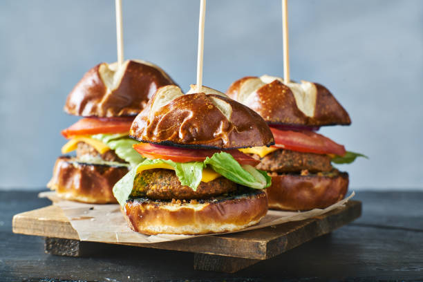three vegan burger sliders with pretzel buns three vegan burger sliders with pretzel buns on wooden tray slider burger stock pictures, royalty-free photos & images
