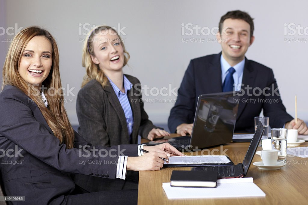Three very happy business people sitting at conference table royalty-free stock photo