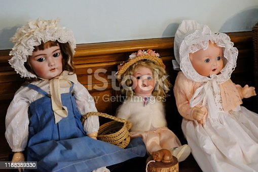 Close-up of three old-fashioned Victorian dolls.