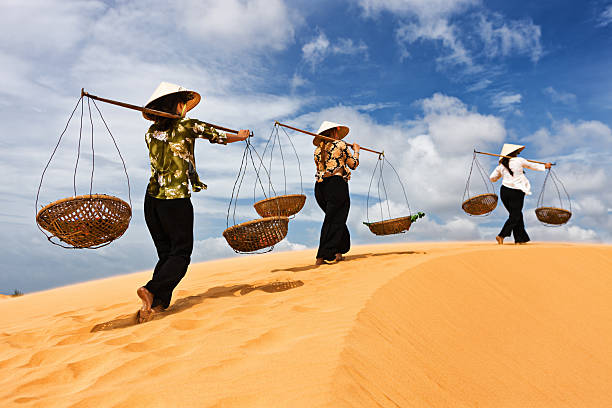 three vietnamese women crossing sand dunes - ao dai stock photos and pictures