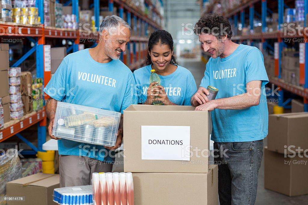 Three volunteers packing eatables in cardboard box stock photo