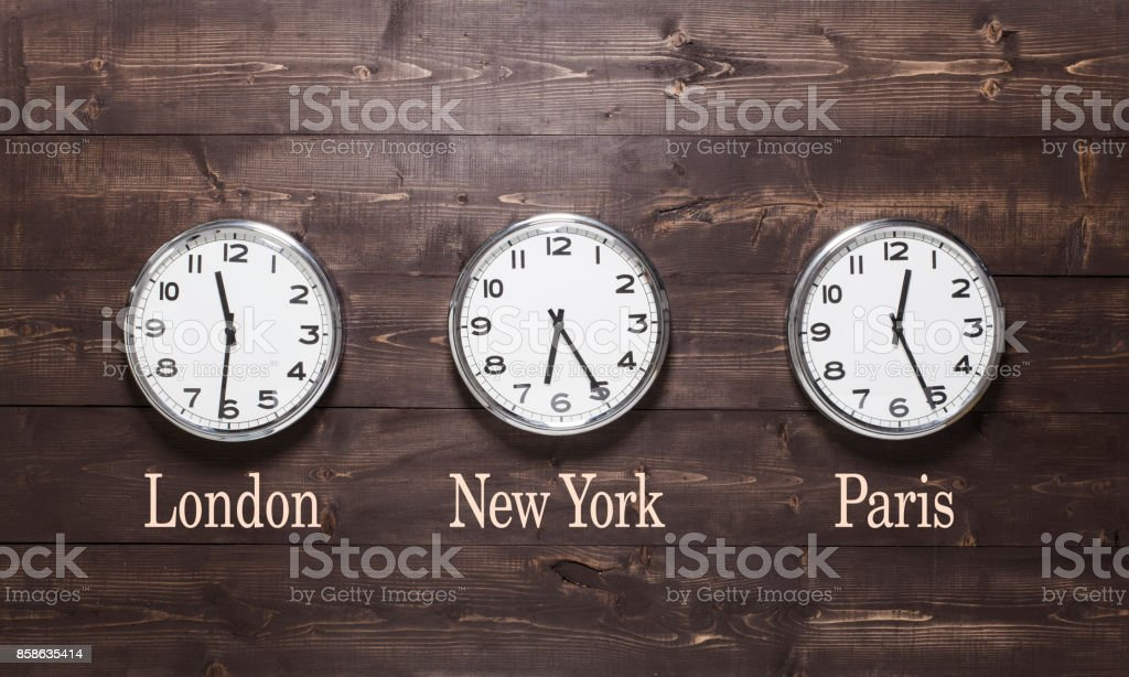 Three wall clocks on different time zones stock photo