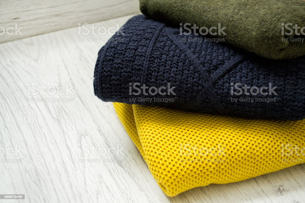 Three warm colour sweaters on a wooden background. Fashionable concept. stock photo