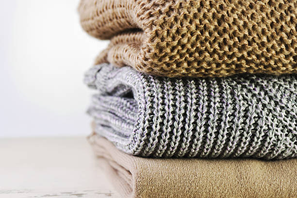 three warm sweaters are stacked on the table  a light – Foto
