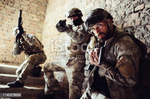 istock Three warriors are standing on stairs and posing. Man in a front is looking straight forward and holding gun. The second guy is taking aim straight forward. The third man is looking up with rifle. 1140379034