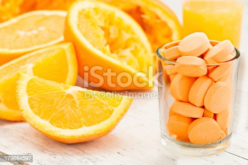 A close up shot of sliced and squeezed oranges a glass of orange juice and a glass full of orange flavored vitamin C Pills. Eat the orange, drink the juice or take a pill.