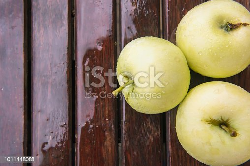 Close-up of few wet golden green apples covered by water drops on brown wet natural old wooden table surface. Background with ripe fruits and copy space. Autumn harvest and healthy eating concepts.